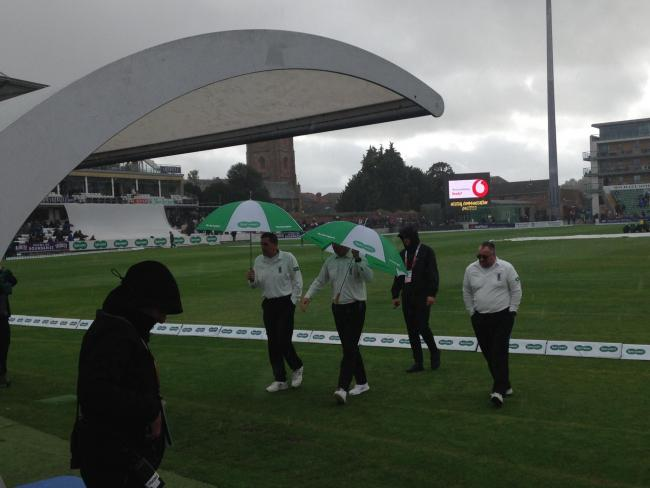 WASHOUT: Umpires Rob Bailey and Alex Wharf leave the field in the rain during the third day