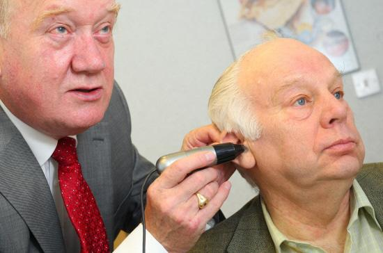 Burnham and Highbridge Weekly News: £5 FOR LEGION: Ted Garrett, hearing aid audiologist, gives Bill Bestford a hearing test