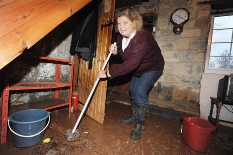 A dispirited Pamela Stach mops her sodden flood. Marks on the wall indicate how high the floodwater was.