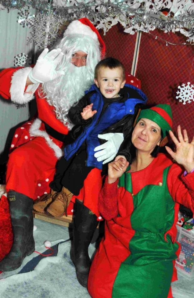 James, two, gives a wave with Santa and elf Kerry Councill.