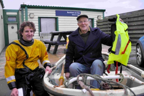 Lifeboat helmsman Ashley Chappell with Roger Ferrier, holding the lifejacket which saved his life.