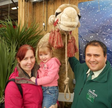 Three-year-old Samantha Wilson from Highbridge and her Mum, Cara Bashford, with Phil Tyzack, Manager of Sanders Garden World and Cracker the camel. Photo: submitted.