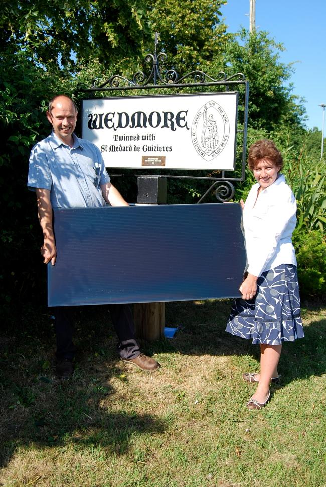 Founders of the Co-operative, Robin Mewes and Vanessa Becker-Hughes, with a solar panel by the Wedmore village sign. Photo: submitted.