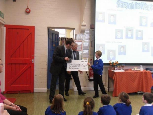 Sydney receives the £250 cheque from Wessex Watermark.
