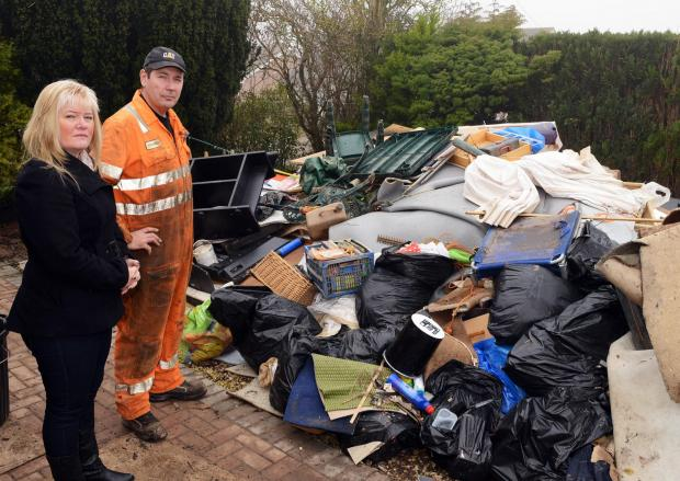 Burnham and Highbridge Weekly News: Lorraine and Adrian Broad pile their possessions outside their home. Photo: Jeff Searle