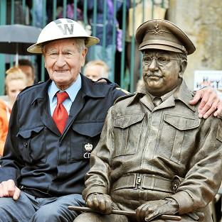 Bill Pertwee who starred in the classic TV comedy Dad's Army sits beside at bronze statue of Captain Mainwaring, played by actor Arthur Lowe, in Thetford, Norfolk