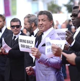 Sylvester Stallone stands with the cast of The Expendables 3, holding up banners reading,