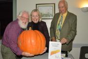 JOHN Page and Wells MP Tessa Munt try guessing the weight of the gigantic pumpkin, watched by Roger Ward.