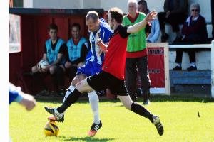 CHALLENGE: Berrow's Luke McErlain (in blue kit) in their match with Watchet Town. Pic: Steve Richardson