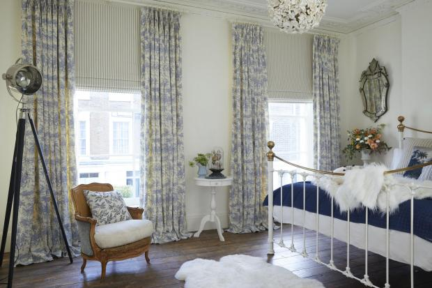 Burnham and Highbridge Weekly News: Daisy Lowe's bedroom with windows made into a feature with Toile de Jouy French Blue curtains, from £123 (127cm w x 137cm d) and blue and white ticking stripe blind, £117, Hillarys. Picture: Hillarys/PA Photo/Handout