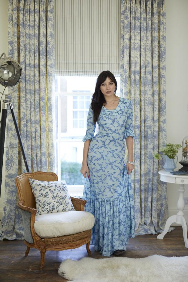 Burnham and Highbridge Weekly News: Daisy Lowe in her bedroom with a pastoral theme conjured with Toile de Jouy French Blue curtains, from £123 (127cm w x 137cm d) and blue and white ticking stripe blind, £117, Hillarys. It has a vintage chair and sheepskin rugs. Picture: Hillarys/PA Phot