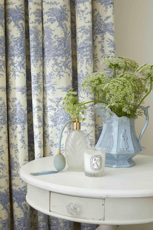 Burnham and Highbridge Weekly News: Toile de Jouy French Blue curtains, from £123 (127cm w x 137cm d) which evoke a pastoral theme in Daisy Lowe's bedroom. It is complemented by a simple arrangement of Cow Parsley, in a pale blue jug. Picture: Hillarys/PA Photo/Handout