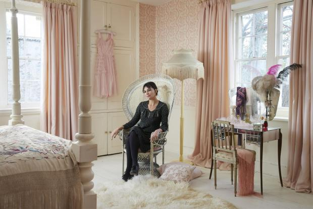 Burnham and Highbridge Weekly News: Pearl Lowe in her bedroom with pink faux silk Clarence Chemise curtains, with thermal lining, from £123 (127d x 137 cm d) Hillarys, Peacock chair, and vintage mirrored dressing table. Picture: Hillarys/PA Photo/Handout