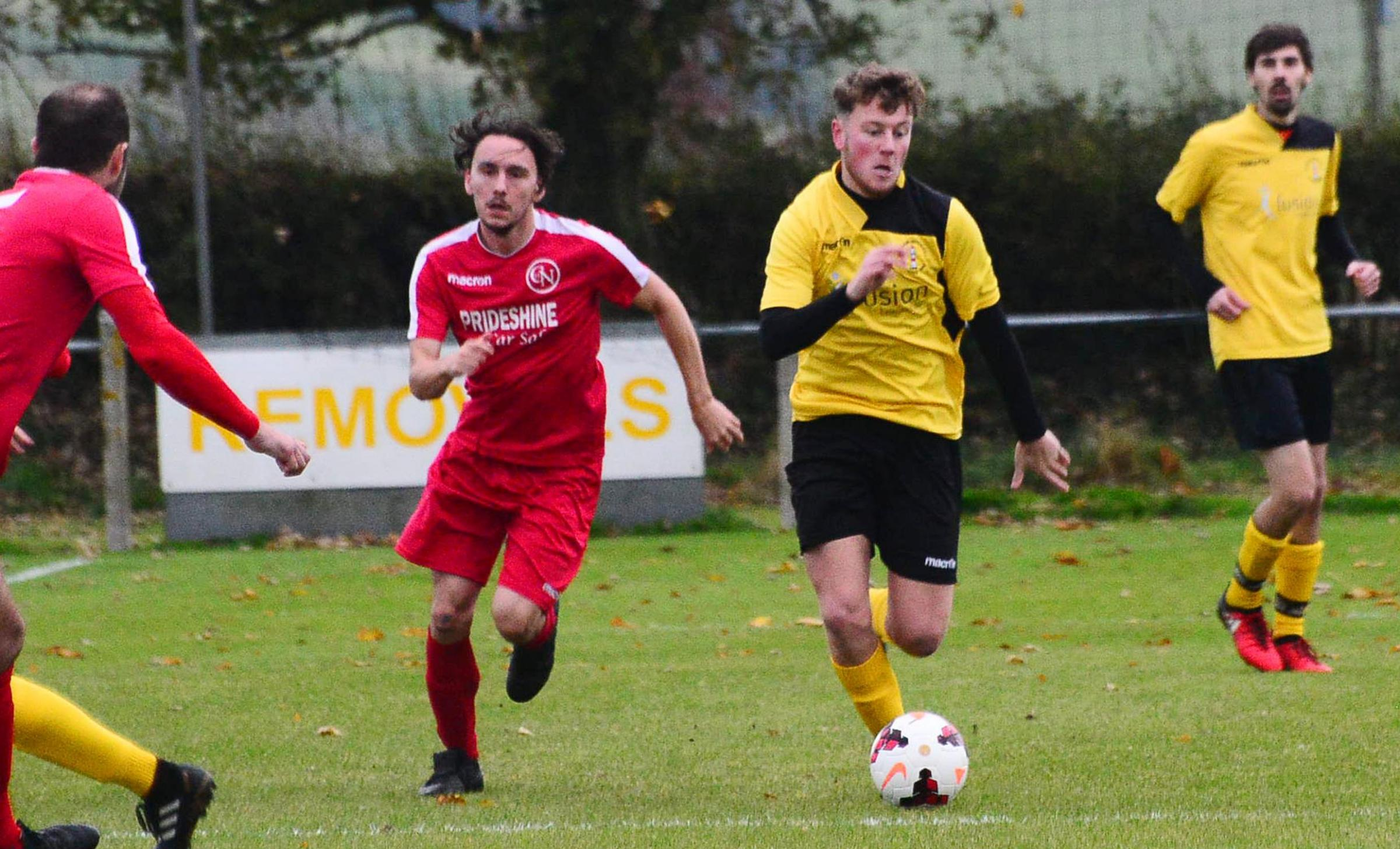FOOTRACE: Burnham United Reserves' Josh Watkins (centre, yellow kit) in action. Pic: Steve Richardson.