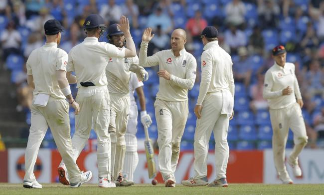 England's Jack Leach, third right, is congratulated by his team mates for taking the wicket of Sri Lanka's Dilruwan Perera during the second day of the second test cricket match between Sri Lanka and England in Pallekele, Sri Lanka, Thursday, Nov.